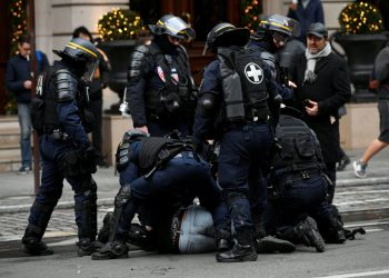 """French CRS riot police apprehend a protester during clashes at a national day of protest by the """"yellow vests"""" movement in Paris, France, December 8, 2018. REUTERS/Piroschka van de Wouw"""